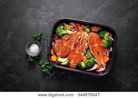 Salmon. Cooking Fresh Raw Salmon Fish Steaks With Vegetables, Broccoli, Carrot And Onion On Black Ba