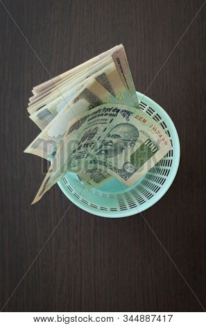 Hundred ruppe notes in a small waste bin. Conceptual stock image for currency de-valuation.