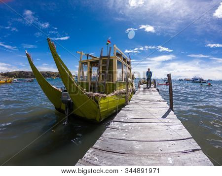 TITICACA / BOLIVIA - MARCH 26, 2018: Traditional Bolivian boat waits on the pier on Titicaca Lake