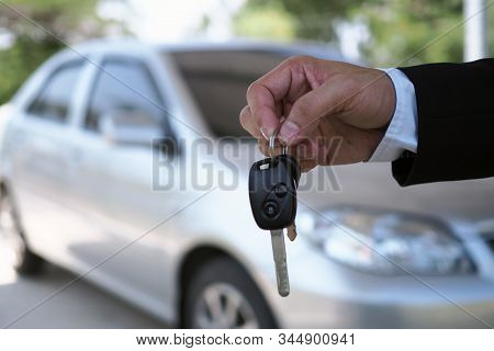 The Car Salesman And The Key To The New Owner.