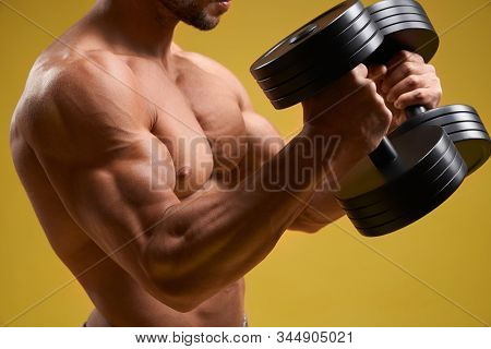 Close Up Of Muscular Young Man With Naked Torso Lifting Heavy Weights. Athletic Shirtless Gentleman
