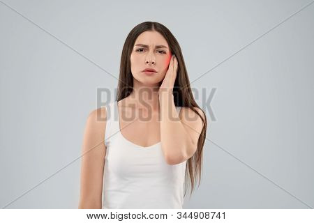 Young Caucasian Woman In White Shirt Over Gray Isolated Background Touching Head With Hand With Pain
