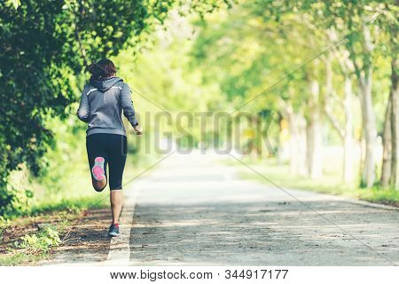 Sporty Asian Woman Runner Running And Jogging Through The Road.  Outdoor Workout In A Park. Weight L