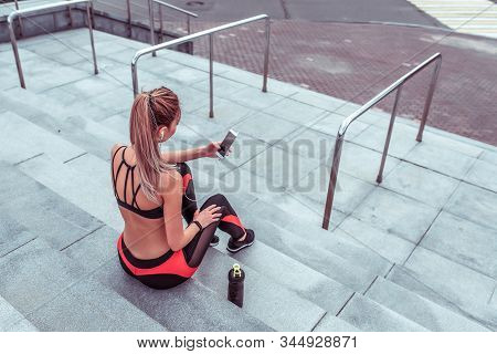 A Woman Resting After Workout, In Summer In City, Sportswear, Mobile Phone Headphones, Listening Mus
