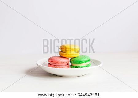 Three Tasty French Macarons On A White Plate And Wooden Table. Pink, Yellow And Green Macarons. Plac