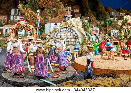 Candelaria, Tenerife, Spain - December 12, 2019: Detail of Christmas Belen -  Statuettes of people and houses in miniature depicting life of old town (Dancing at market square)