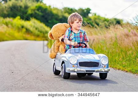 Little Preschool Kid Boy Driving Big Toy Car And Having Fun With Playing With His Plush Toy Bear, Ou