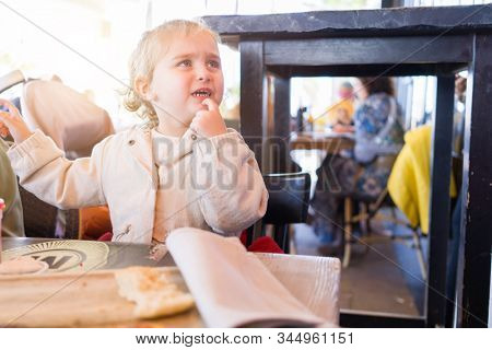 Beautiful toddler child girl sitting on baby highchair  crying and screaming