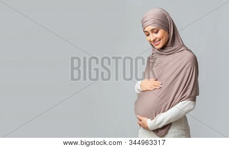 Pregnant Muslim Woman In Hijab Embracing Her Belly And Posing Over Gray Background With Free Space,