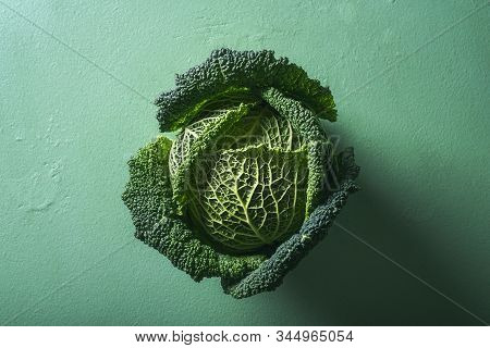 Single Cabbage On Aqua Menthe Table. Above View Of Green Savoy Cabbage In Sunlight. Organic Food. De