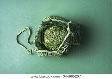 Organic Savoy Cabbage In A Reusable Shopping Bag On Aqua Menthe Table. Fabric Net Bag With Fresh Cab