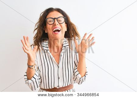 Middle age businesswoman wearing striped dress and glasses over isolated white background celebrating mad and crazy for success with arms raised and closed eyes screaming excited. Winner concept