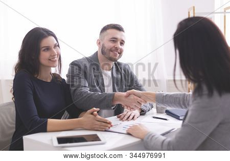 Mortgage Consultation. Young Family Handshaking With Expert, Ready To Sign Credit Contract At Office