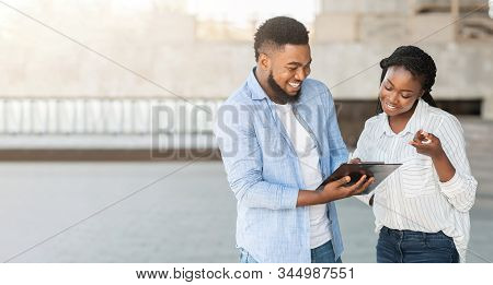 Social Survey Concept. Black Millennial Guy Answering Questionnaire Of Female Interviewer Outdoors,
