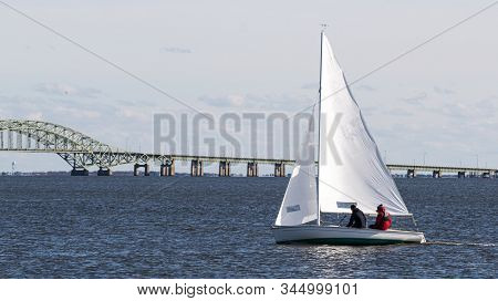 Two People Sailing North In A Two Person Sailboat In The Winter Wih The Great South Bay Bridge In Th
