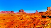 Horse at John Ford Point with towering red sandstone formations of Sentinel Mesa, Merrick Butte and Mitten Buttes in Monument Valley Navajo Tribal Park desert landscape on the border of Arizona and Utah, United States poster