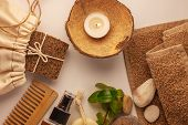 Spa and wellness concept, natural coffee scrub soap in eco bag, oil cosmetics spray, peeling sand stone, towel,wooden haircomb. Beige dayspa set.Brown pastel bathroom accessories and products top view poster