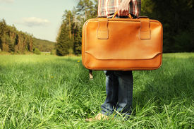 Man With Travel Bag Standing On Green Lawn
