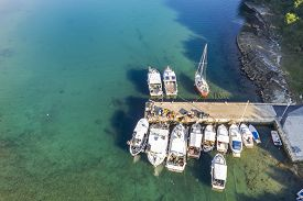 An Aerial Shot Of Runke Bay With Small Port And Pier With Fishing Boats And Fishing Gear In Premantu