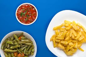 French Fries On A White Plate In The Blue Background. French Fries With Vegetable Salad Fast Food To