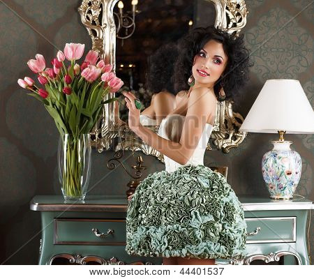 Beautiful Glamorous Woman In Retro Interior With Vase Of Flowers. Reflection