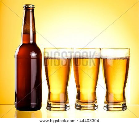 Three Glasses And Bottle Of Fresh Light Beer On Yellow Background