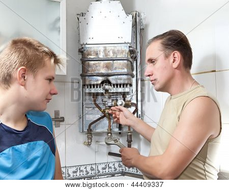 father and the son together repair a gas water heater.