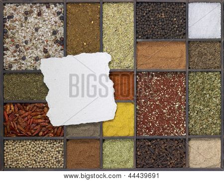 lots of various different spices in a framed dark wooden box with a chit of paper on it seen from above poster