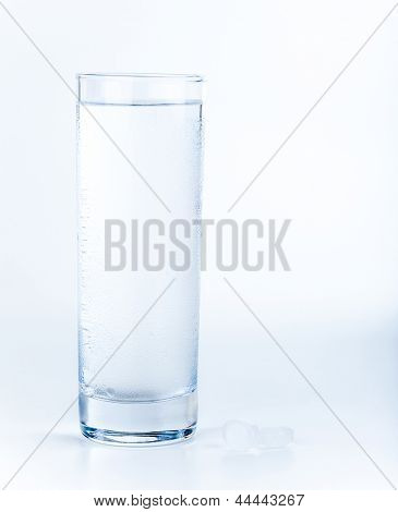 Glass with pure water and pills on the table isolated on white background, healthy lifestyle, purified aqua, medical concept
