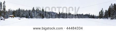 Panorama Of Frozen Lake With Log Cabin