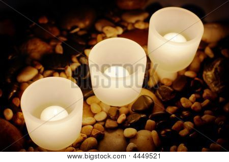 Candels buring at night on top of rocks. poster
