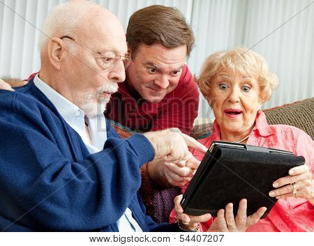 Adult son enjoys showing his parents how to use the new Tablet PC he gave them as a holiday gift.