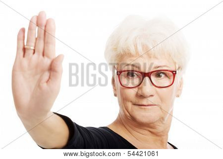 An old lady showing stop sign by hand. Isolated on white.