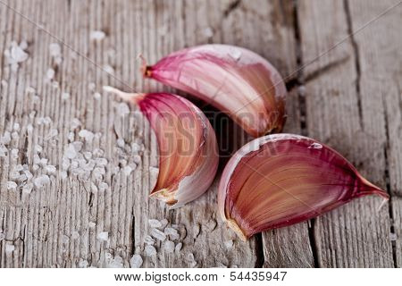 fresh garlic slices and sea salt on rustic wooden background