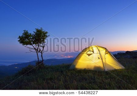 Night landscape with a tent in the mountains. The light from the lantern in a tent. Camping in the countryside. Crimea, Ukraine, Europe