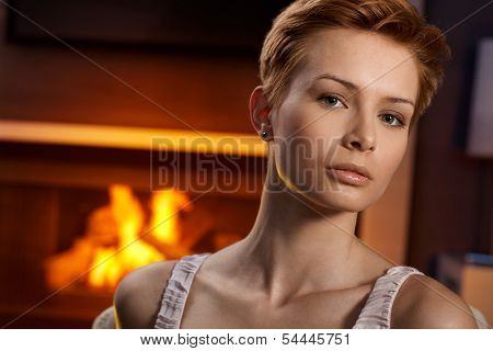 Portrait of serious young woman by fireplace.