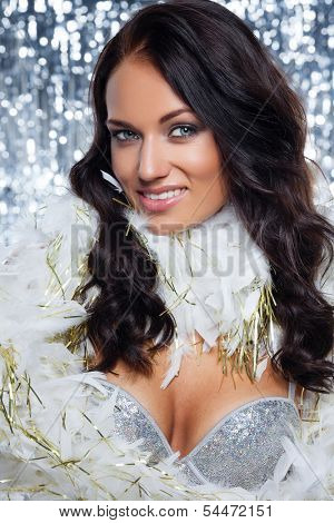 Beautiful young woman in celebration winter styled costyme holding heart shape in her hands