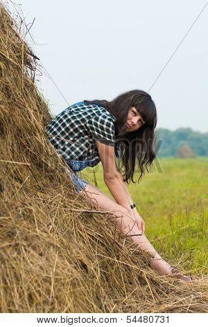 Portrait Of Pretty Brunette Lying On Haystack
