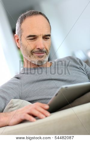 Mature man at home websurfing on internet  poster