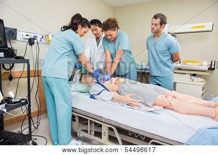 Female nurse performing CRP on dummy patient while doctor and colleagues looking at it in hospital room