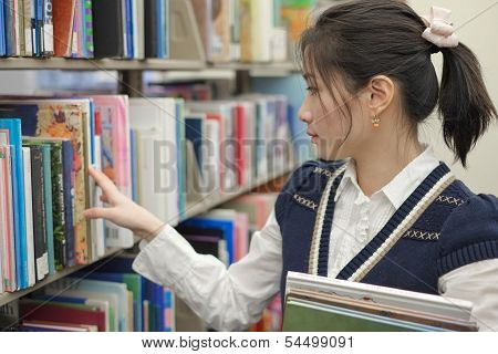 Woman Looking For Books From Shelf