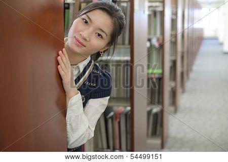Girl Hiding Behind Bookshelf