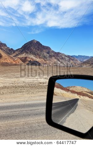 A great American roads. Road in dry and desert wildlife in Death Valley is reflected car mirror