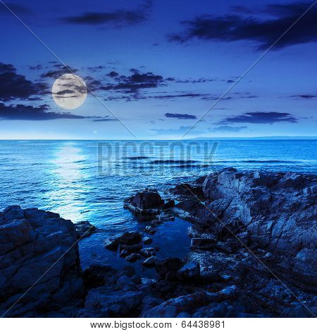 Calm Sea With Boulders On Coast At Night