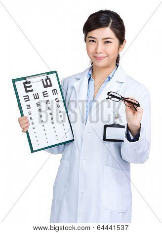 Female oculist holding eyechart and glasses