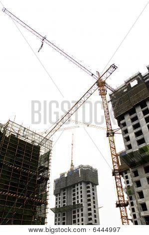 Construction Site Tower Cranes Against White Sky.