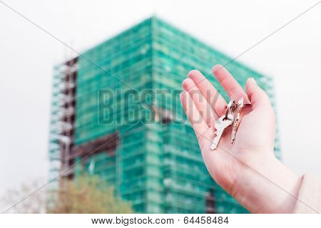 A real estate agent holding keys to a new apartment in her hands. Building under construction Real estate industry