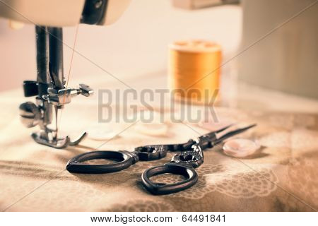 Antique scissors on fabric against vintage sewing machine threaded with cotton - vintage tone effect added poster