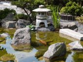 Details of Japanese garden with water pond and stone pagoda poster