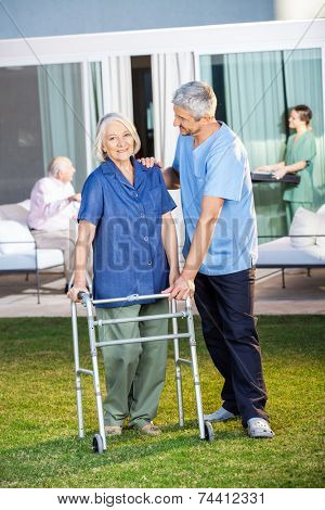 Portrait of senior woman being assisted by male caretaker in using Zimmer frame at nursing home lawn
